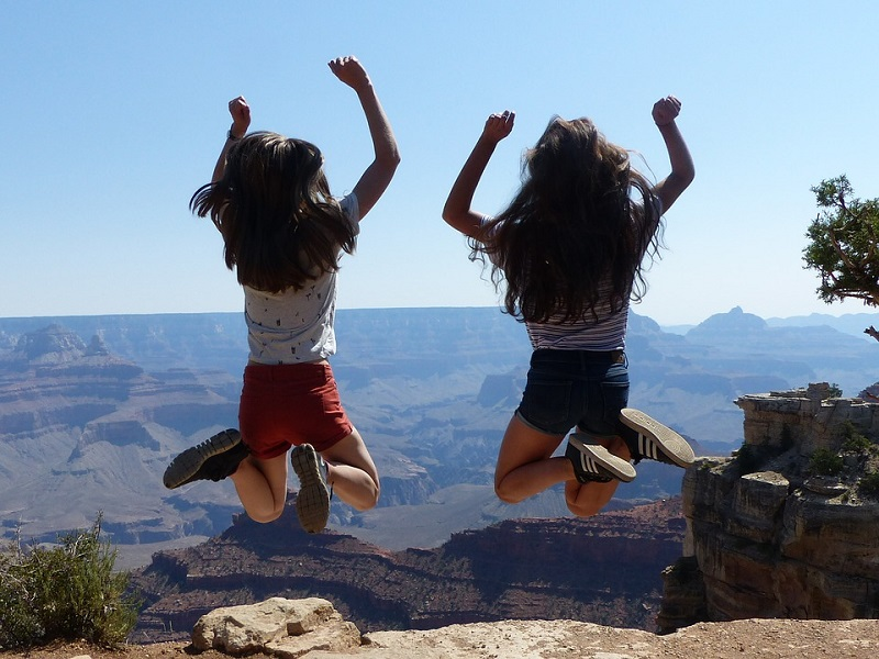 two girls jumping near the Grand Canyon