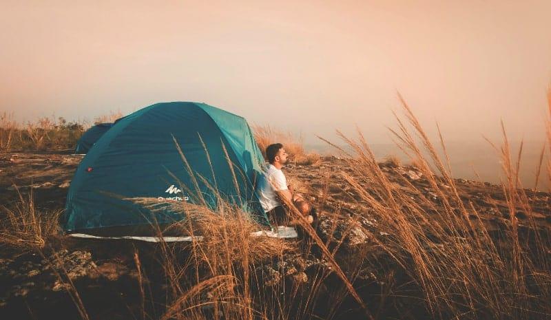 man sitting near the tent