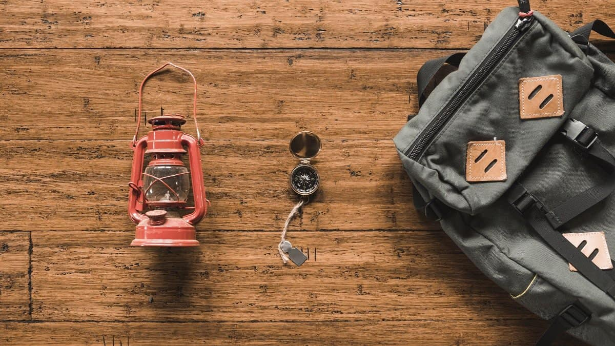 backpack and lantern on the wooden background