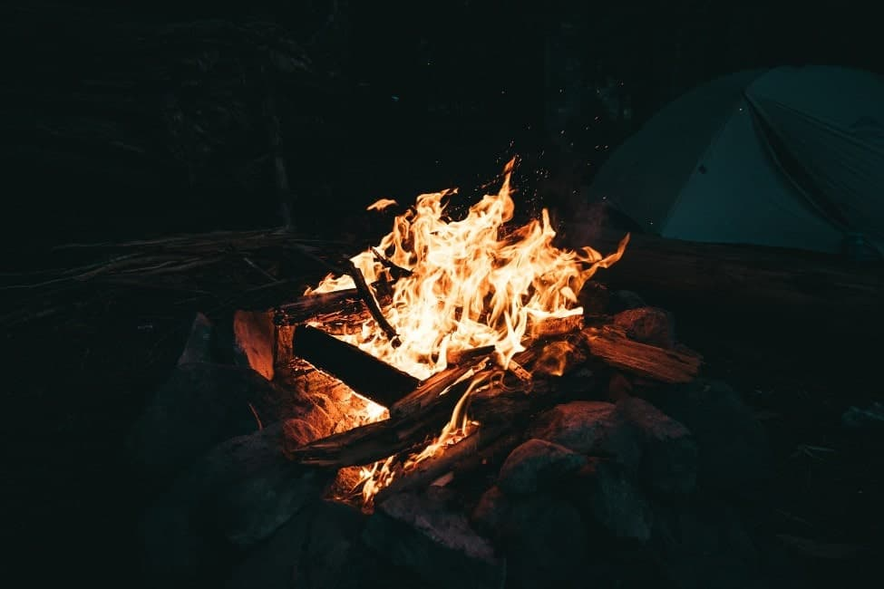 photo of a campfire with a tent in the background